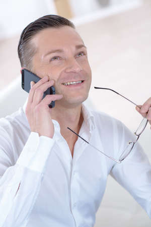 smiling mature businessman talking on phone in the street