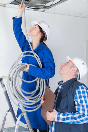 female eleectrician putting pipes in the ceiling