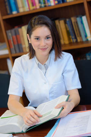 doctoral: young female doctor studying in library Stock Photo