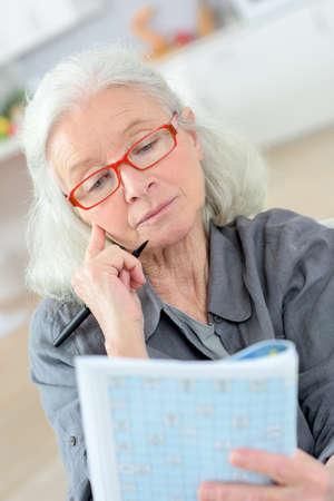 Elderly woman doing puzzle in magazine