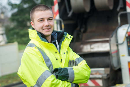 young garbage collector standing near his truck Stock Photo - 89713358