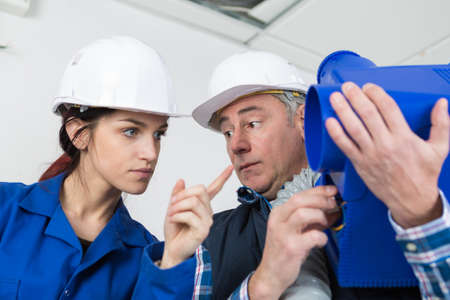 tutor looking in surprise at female apprentice pointing at equipment Stock Photo