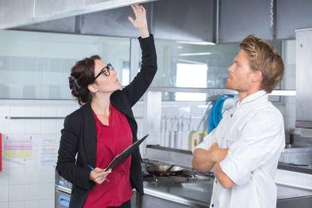 kitchen inspector feeling around overhead extractor Stockfoto