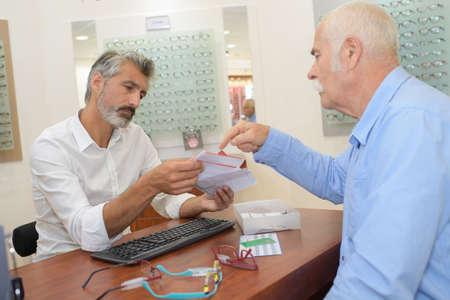 senior male optician offering glasses frames to elderly client Imagens