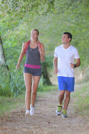 young healthy couple running in forest Stock Photo