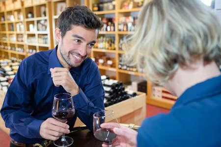 Een man die de wijnproeverende klanten bijwoont Stockfoto