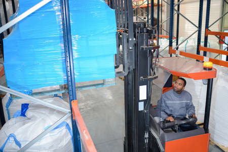 A man on a forklift loading boxes at a warehouse