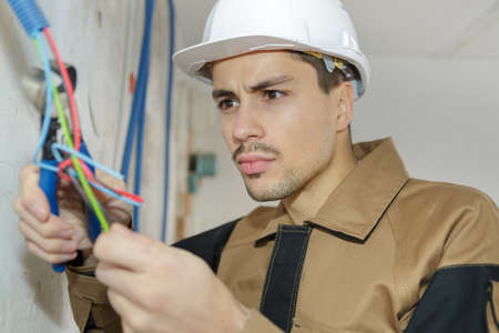 electrician attaching wires to socket in new building Stock Photo