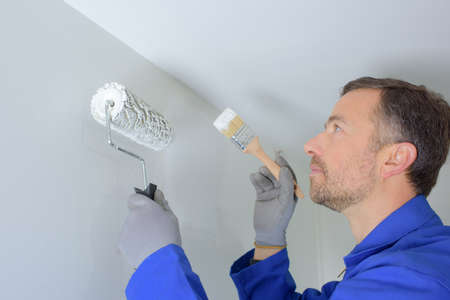 A man painting the wall in a DIY concept Stock Photo