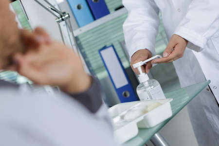 A man disinfecting his hand with blue alcohol in a hospital