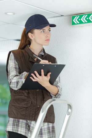 A woman inspecting the exit sign Stock Photo