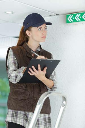 Una mujer inspeccionando el letrero de salida Foto de archivo - 90010509