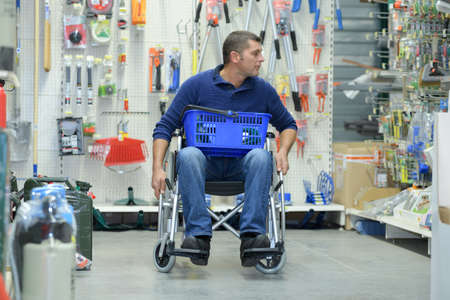 consumerism: man on the wheelchair going shopping in the hardware