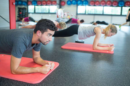 Beautiful sport people doing plank in modern fitness hall 스톡 콘텐츠