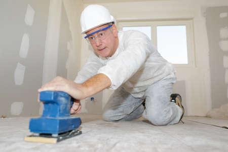 A builder polishing the floor