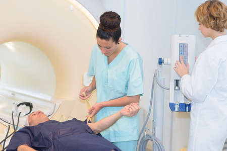 A radiologic technician female patient lying on a ct scan bed