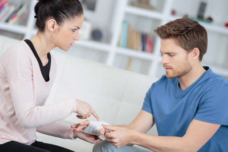 A woman questioning a man about his bandaged hand Stock Photo