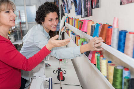 Two women choosing thread reels in a sewing store Stock Photo