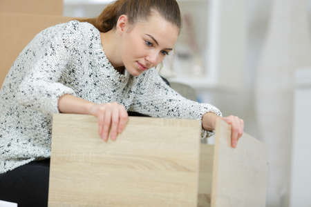 A young woman assembling the parts of furniture