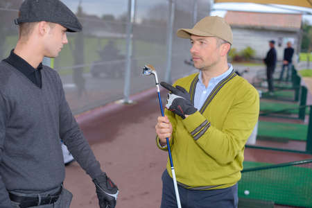 Two men training golf ball with bucket on rough grass Stock Photo