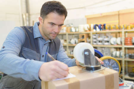 Man writing label for cardboard box