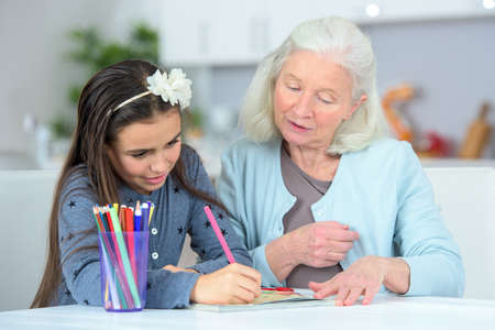 Grandchild drawing at home with grandmother