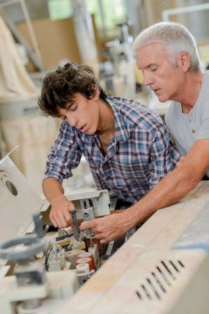 A father teaching carpentry to his son
