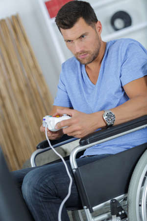 man in wheelchair playing computer game