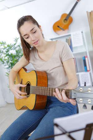 joyful girl playing the guitar at home