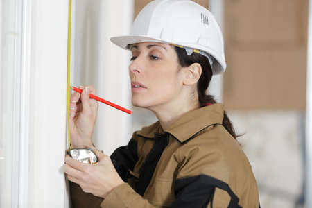 female constructor showing measuring the wall Stock Photo