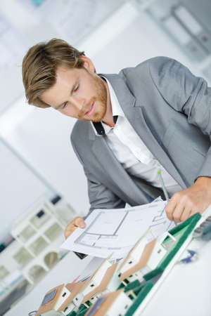 Architect with plans and scale reproduction Stock Photo