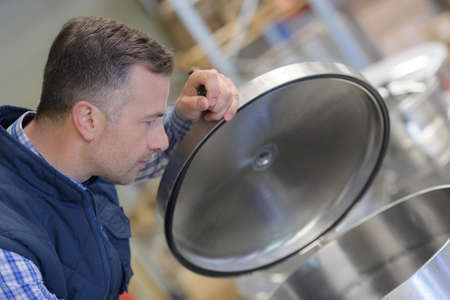 man opening a large metal container in a factory Stock Photo