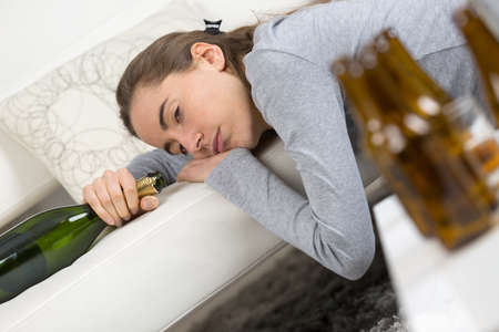 alcoholic addict woman lying on the sofa hangovered with bottles