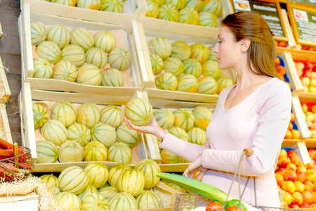Woman choosing cantaloups Stock Photo