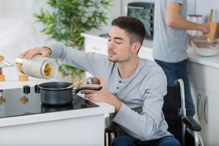 disabled young man in wheelchair cooking a meal in kitchen Stock Photo