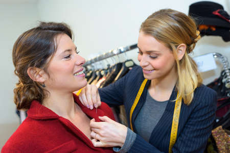 cheerful smiling woman trying on coat in womens cloth store
