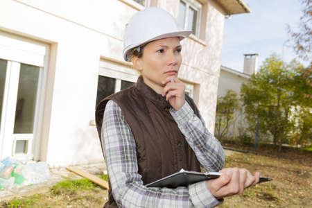 contemplative woman stood outside property holding clipboard