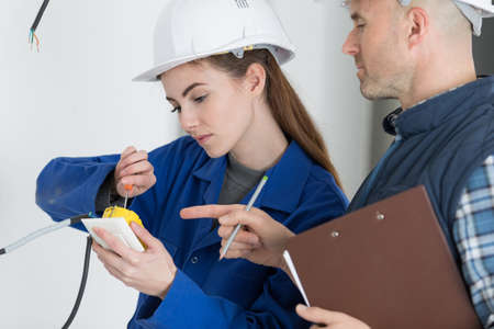 electrician and his female apprentice ajusting socket Stockfoto
