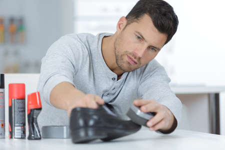 man cleaning his shoe Stock Photo