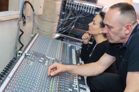 sound engineers working at mixing panel in recording studio