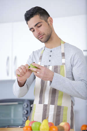 man cuts fruits in the kitchen