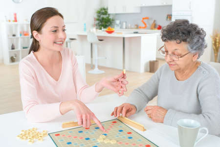woman playing a game of word puzzle with an old woman