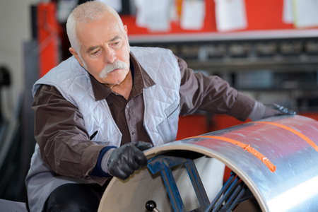 senior handarbeider bewegende gasflessen in de metaalindustrie