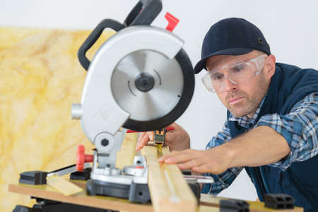 carpenter using circular saw cutting wooden board in wood workshop