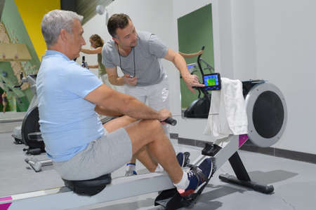 senior man in gym using a rowing machine Stock Photo