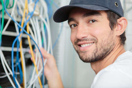 young adult electrician in front of fuse switch board