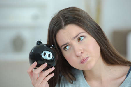 Exasperated woman holding piggy bank