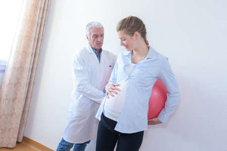 Pregnant woman leaning back against aerobic ball
