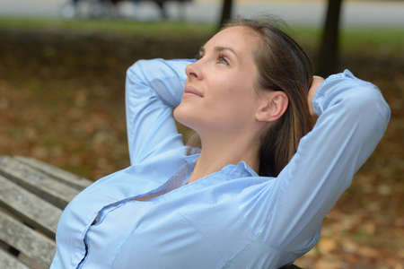 Woman leaning back on park bench Stock Photo