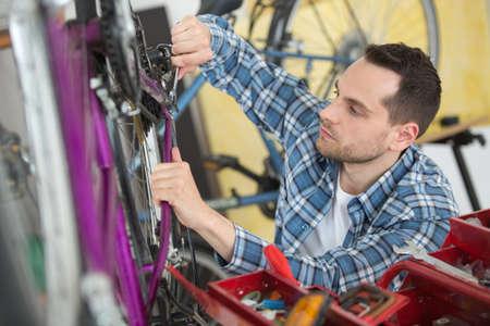 seller fixing bike in sport store Stock Photo